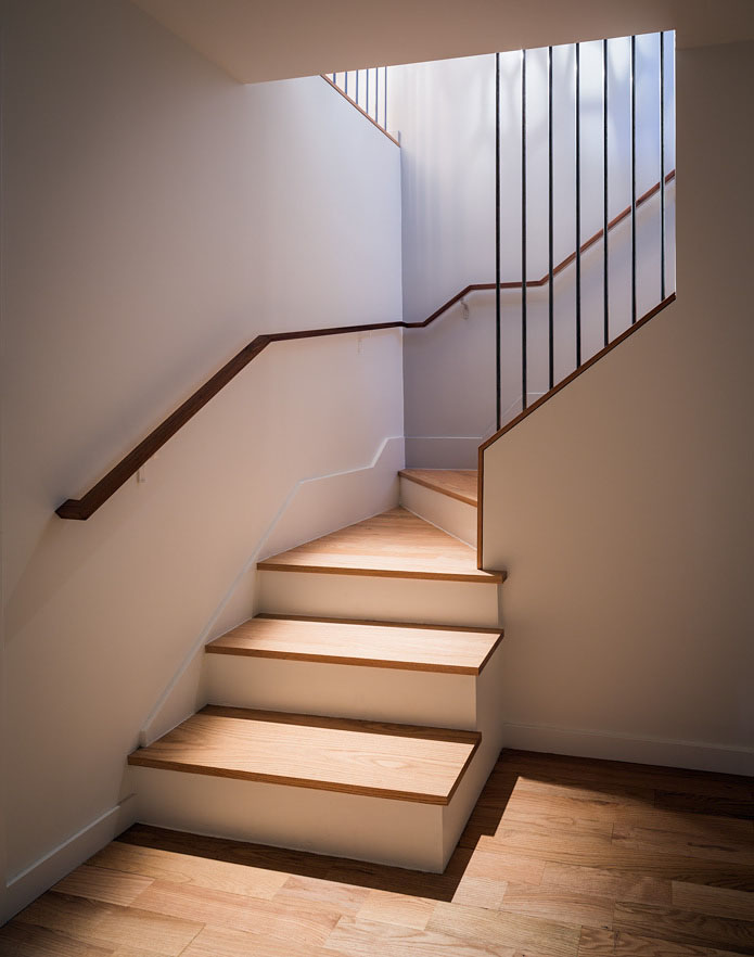 "A tremendous amount of lighting is being done to the lower stairwell in order to show the intent of the designer. The shadow pattern from the pendant lamp upstairs has been strengthened, and the stairs have been lit ""from the inside out"" in order to draw attention to the keyhole cutout and the strong graphic lines of the handrail and bars."
