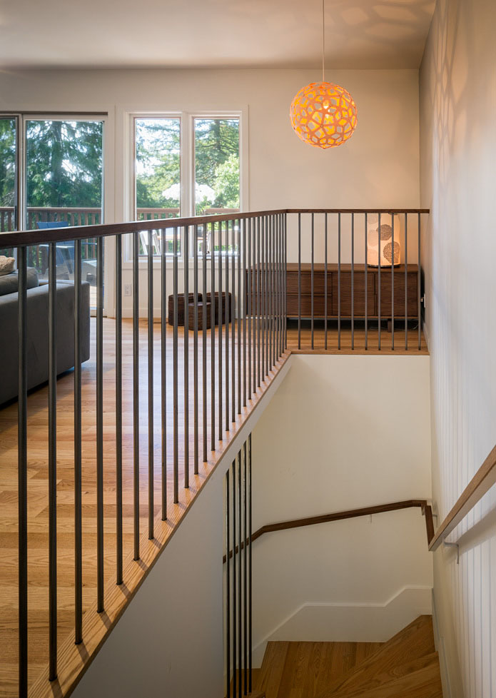 This angle, intended as a companion to the photo above, demonstrates how the vertical rails are continuous with the upstairs railing, and again shows off the banister and pendant lamp.
